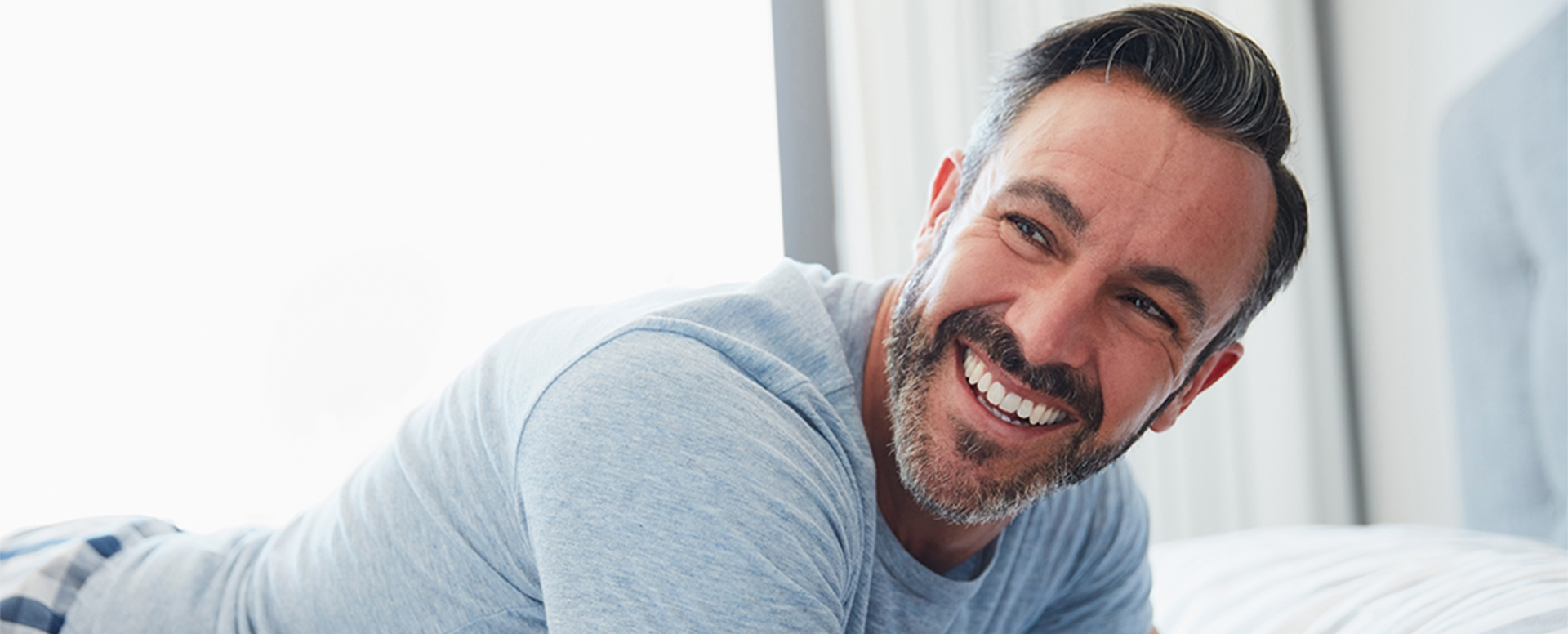 man smiling on bed